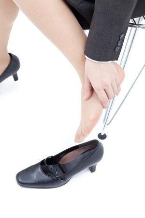 hands off: Las mujeres de masaje piernas cansadas, aisladas sobre fondo blanco