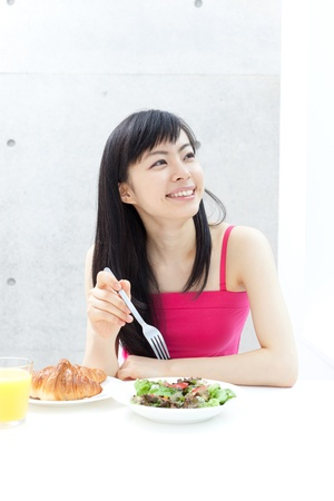 beautiful young girl eating breakfast  photo