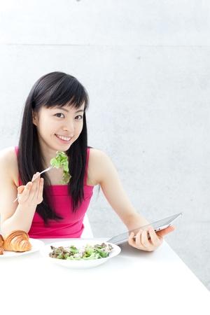 ni�a comiendo: hermosa joven que come el desayuno y el uso de Tablet PC