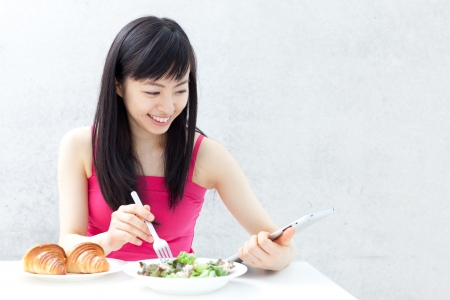 beautiful young girl eating breakfast and using tablet computer  photo