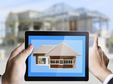 3d touchpad ,hand holding a touchpad pc with home construction  photo