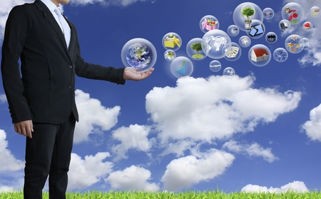 palm computer: holding a glowing earth globe in his hands with blue sky background Stock Photo