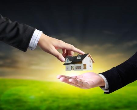 real estate background: house in human hands, businessmen