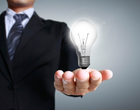 business environment: Light bulb in a hand on a gray background