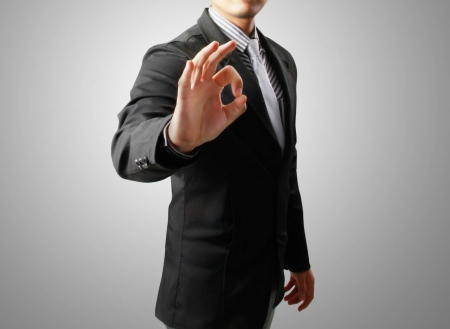 alright: business man with hand OK gesture on the gray background