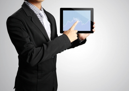 article marketing: Businessman pointing on touch screen tablet in a hand Stock Photo
