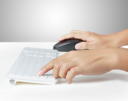 Hands typing on the remote wireless computer keyboard photo