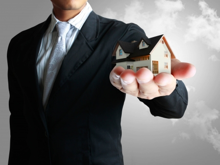 Businessman,house in human a hands Stock Photo - 14419223