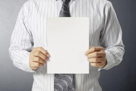 Business man handing a blank business a4 card over  photo