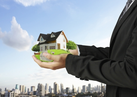 real estate investment: Business man house in human hands