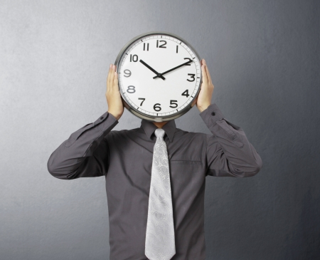 obscured face: Businessman with alarm clock on head
