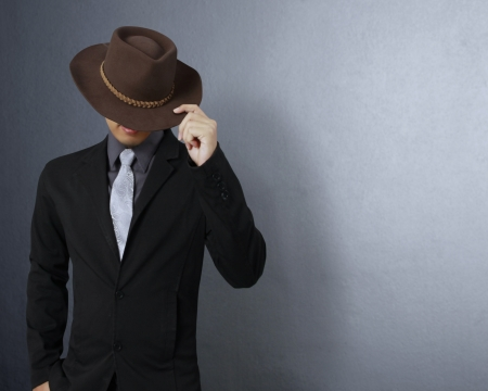 Fashionable man with hat on gray background