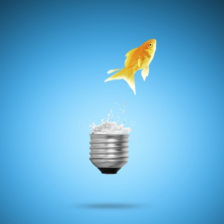 Goldfish jumping out light bulb photo