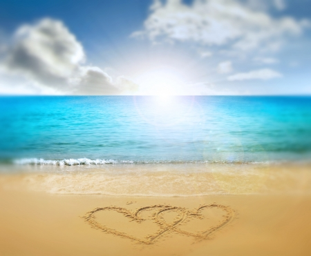 two ensambled hearts drawn in a sand of a beach photo