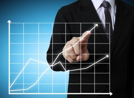 economia: Los hombres de negocios mano empujando gr?fico de escritura Foto de archivo