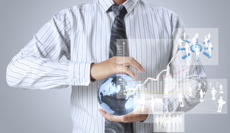international trade: holding glowing earth globe and  financial symbols coming from hand  Stock Photo