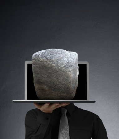 business man holding a laptop and Stone  photo