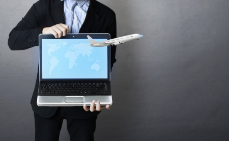laptop with plane flying away from it in hand  Business man  photo
