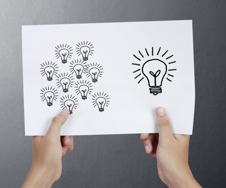 Business man drawing light bulb in a4 photo