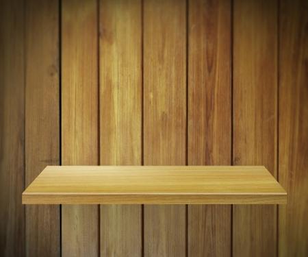 Empty shelf for exhibit on wood background photo