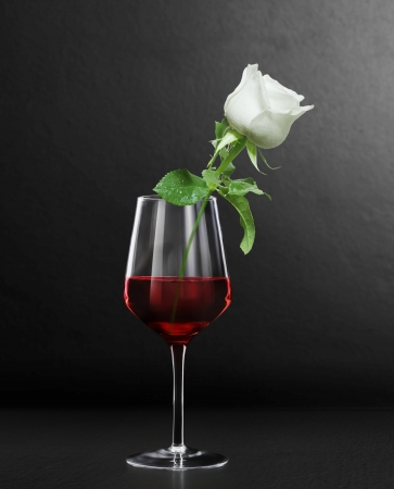 merlot: Glass of red wine and a roses