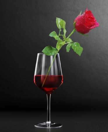 syrah: Glass of red wine and a roses