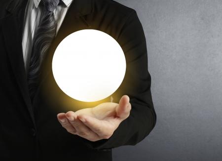 bola de cristal: Empresario mano que sostiene la bola de cristal