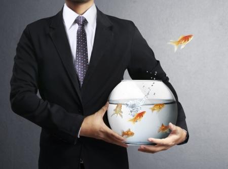 Homme d'affaires de vol goldfishes de l'un à l'autre