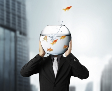 Business man and flying goldfishes from one to another
