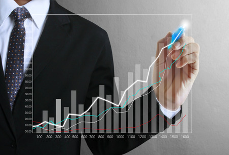 share prices: Business man hand drawing a graph