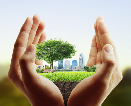 green earth: human hand holding the city