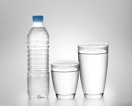Bottle of water with glass on white background  Stockfoto