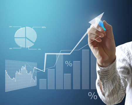 financial figures: man drawing a graph on a glass wall  Stock Photo