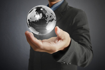 hands holding earth: holding a glowing earth globe in his hands.  Stock Photo