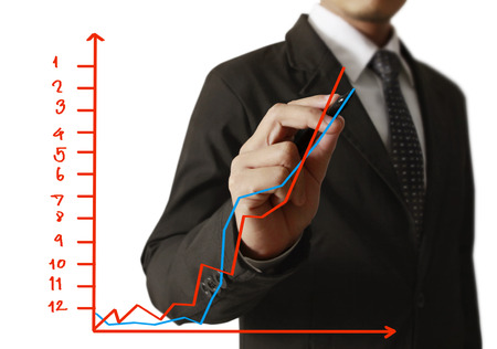 growing business: businessman hand writing a business graph on a glass wall