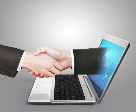ecomerce: hand comes right out of the laptop screen to shake hands Stock Photo