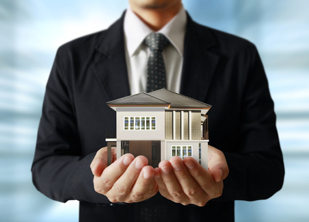 real business: Holding house representing home ownership and the Real Estate business Stock Photo