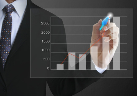Businessman drawing graphics a growing graph photo
