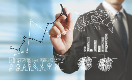 financial concept: Businessman drawing graphics a growing graph