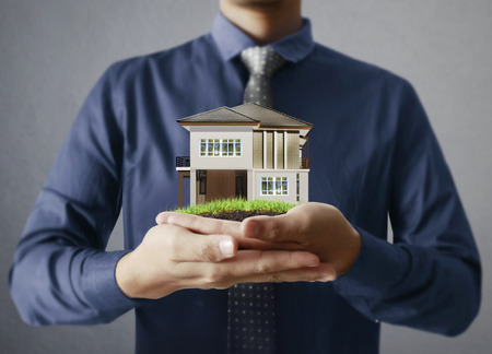 smilie: Businessman holding a house model Stock Photo