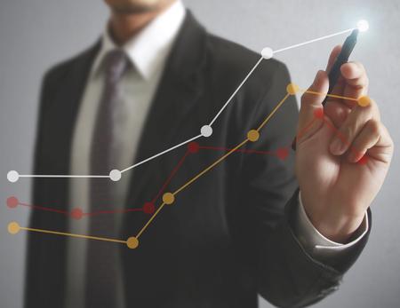 ganancias: Gráficos del dibujo del hombre de negocios un gráfico de crecimiento