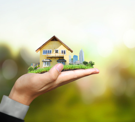 invest: Business man house in human hands Stock Photo