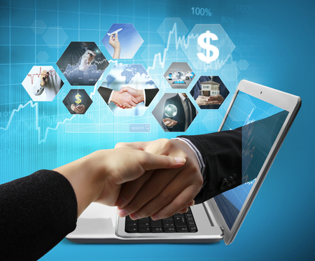 Business  hand reaching out from screen laptop shake Hand from notebook Stock Photo