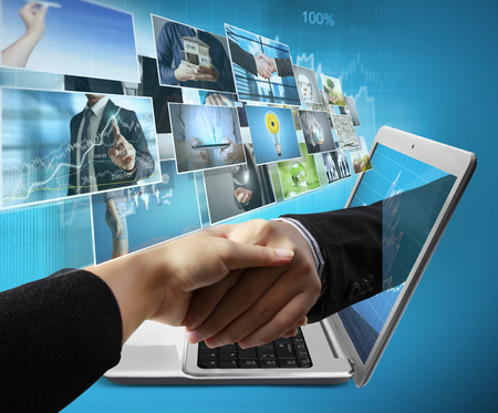 Business  hand reaching out from screen laptop shake Hand from notebook Standard-Bild