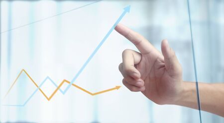 Hand touching a graphs of financial indicator and accounting market economy analysis chart Foto de archivo