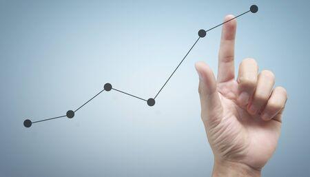 Hand, die ein Diagramm des Finanzindikators und des buchhalterischen Marktwirtschaftsanalysediagramms berührt