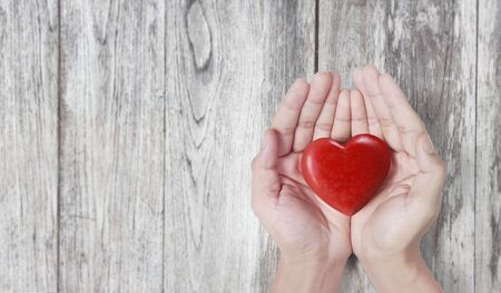 Hands holding a red heart, heart health, and donation concepts