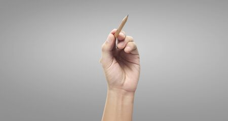 Pencil in hand on a Gray background
