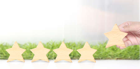 Wooden five star in hand shape. The best excellent business services rating customer experience concept