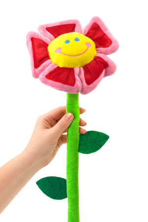 Toy flower in hand isolated on white background photo